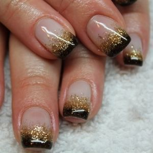 Photo of black french tip nails with gold glitter