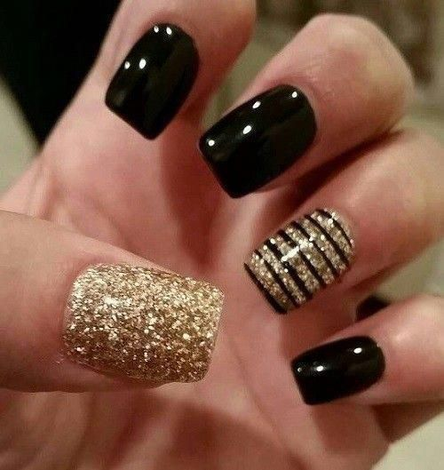 Photo of black and gold nails with black stripes as acccent