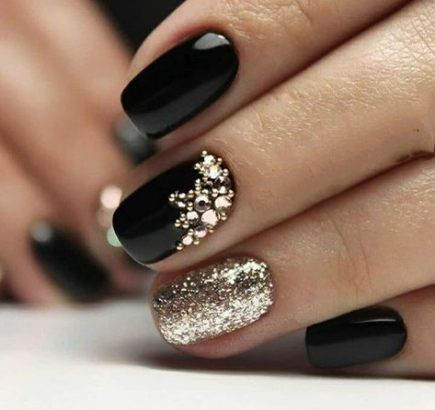 Photo of black and gold nails with glitter